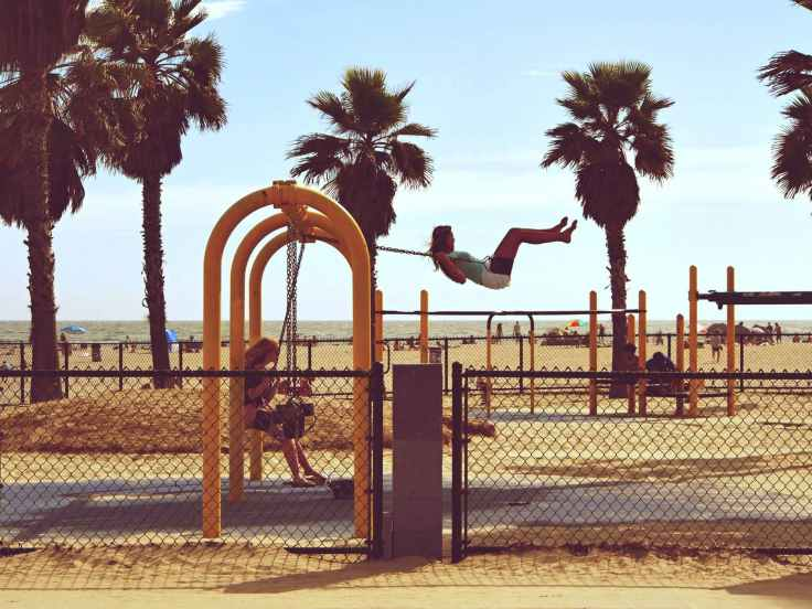 woman playing swing near beach